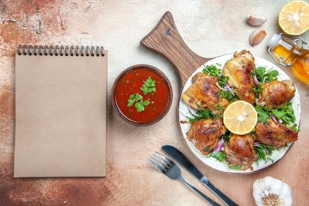 Bovenaanzicht van kip kip met citroenkruiden op het bord olie vork mes crème notebook