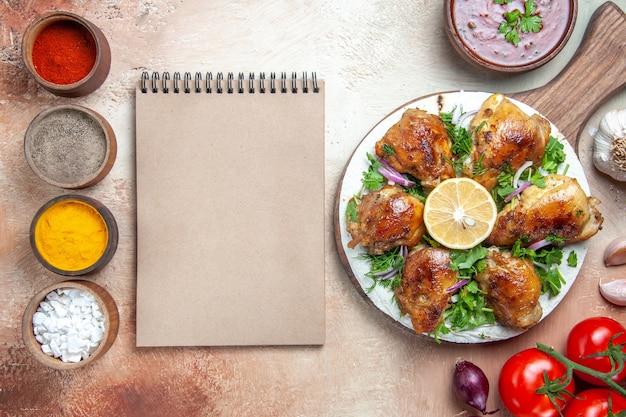 Bovenaanzicht van kip kleurrijke kruiden saus kip met kruiden ui tomaten room notebook