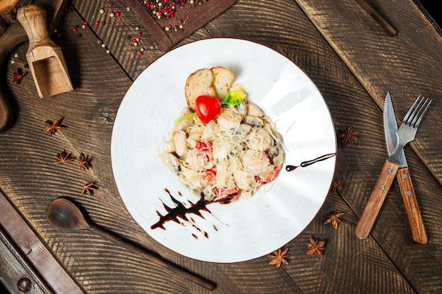 Bovenaanzicht van kip tagliatelle met champignons op de houten tafel
