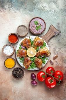Bovenaanzicht van kip tomaten ui kleurrijke kruiden kip met kruiden citroen