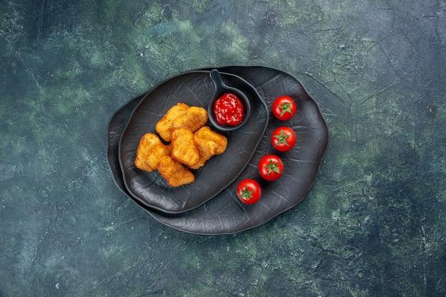 Bovenaanzicht van kipnuggets en ketchup tomaten in zwarte platen op donkere ondergrond