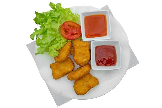 Bovenaanzicht van kipnuggets met saus en sla gestanst op wit geïsoleerd