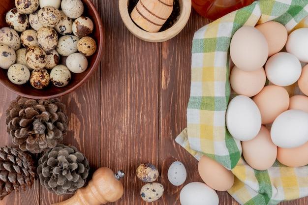 Bovenaanzicht van kippeneieren op een gecontroleerd tafelkleed en kwarteleitjes op een kom met dennenappels geïsoleerd op een houten achtergrond