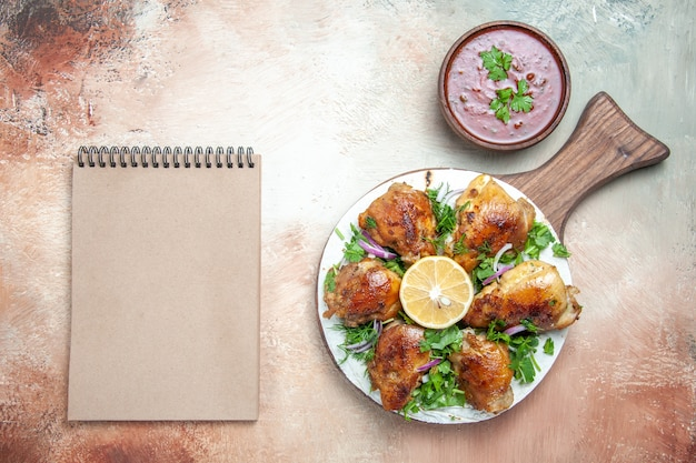 Bovenaanzicht van kippensaus kip met kruiden ui op lavash op het bord crème notebook