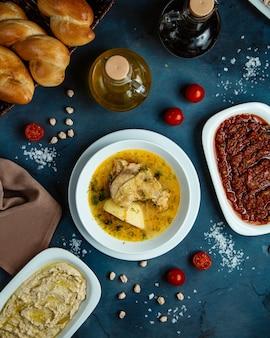 Bovenaanzicht van kippensoep en bijgerechten en brood