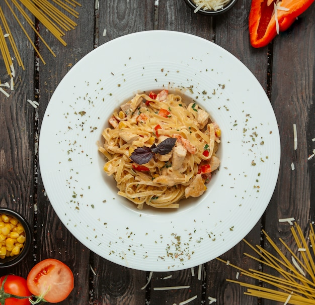 Bovenaanzicht van kippenspaghetti met paprika en peterselie