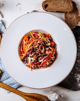 Bovenaanzicht van kipsalade met gehakte kool en kleurrijke paprika in een plaat