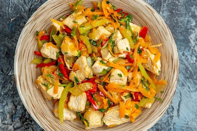 Bovenaanzicht van kipsalade met groenten op lichte ondergrond