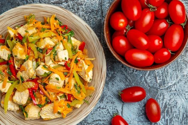 Bovenaanzicht van kipsalade met tomaten op lichte ondergrond