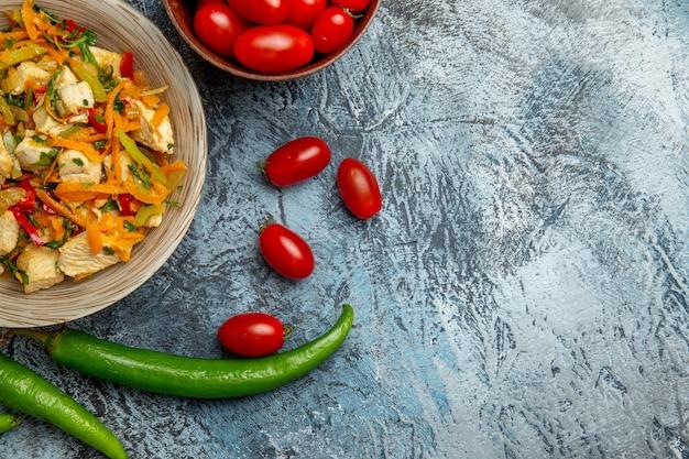 Bovenaanzicht van kipsalade met verse tomaten op lichte ondergrond