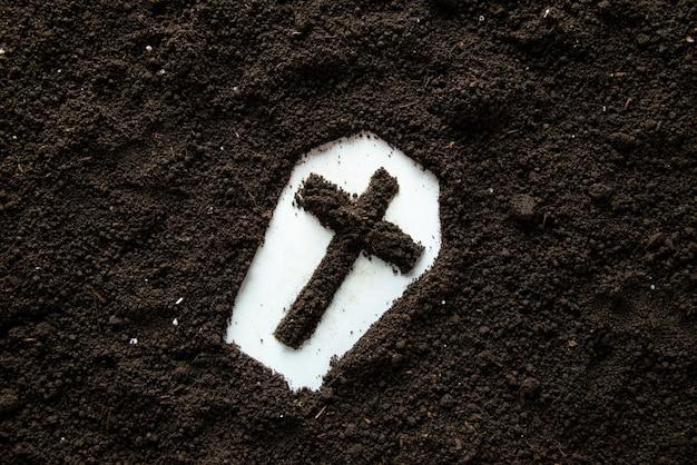 Bovenaanzicht van kistvorm met kruis en bruine grond
