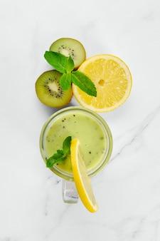 Bovenaanzicht van kiwi en citroen smoothie met munt op marmeren achtergrond