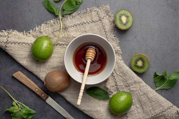 Bovenaanzicht van kiwi en kom met honing