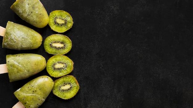 Bovenaanzicht van kiwi ijslollys met kopie ruimte