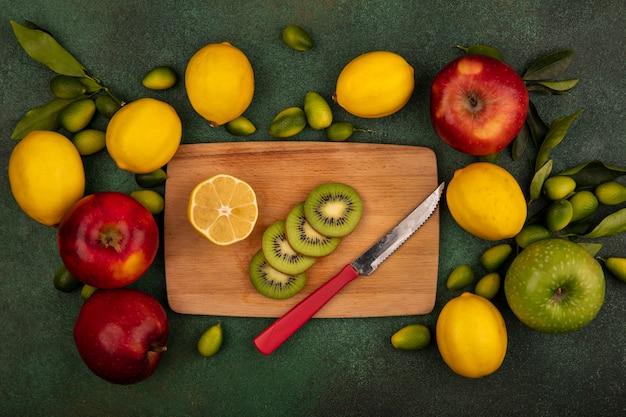 Bovenaanzicht van kiwiplakken op een houten keukenbord met mes met citroenen en kleurrijke appels geïsoleerd op een groen oppervlak