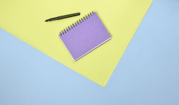 Bovenaanzicht van kladblok en pen op gekleurd papier