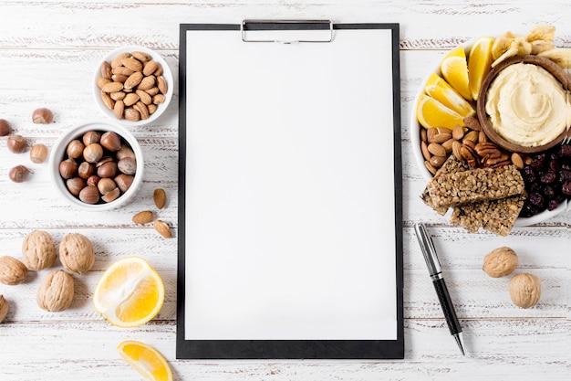 Bovenaanzicht van kladblok met assortiment van noten en graanrepen