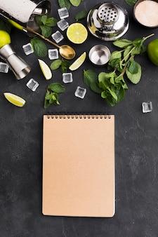 Bovenaanzicht van kladblok met cocktail essentials en ijsblokjes