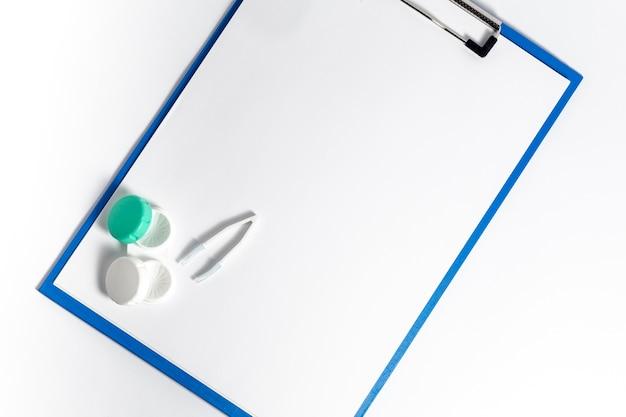 Bovenaanzicht van kladblok met contactlenzen geval