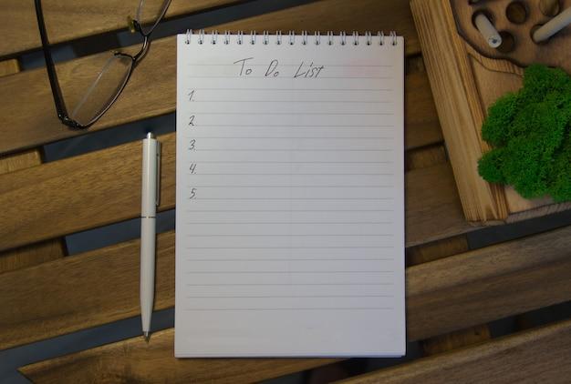Bovenaanzicht van kladblok met doelenlijst, bril op houten tafel, doelen concept
