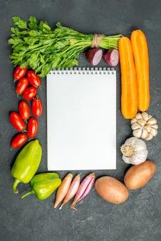 Bovenaanzicht van kladblok met groenten eromheen op donkergrijze achtergrond