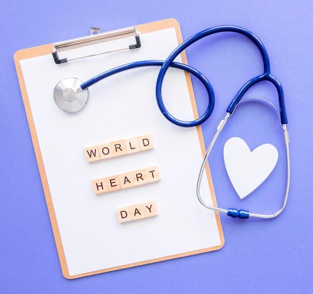 Bovenaanzicht van kladblok met papier hart en stethoscoop