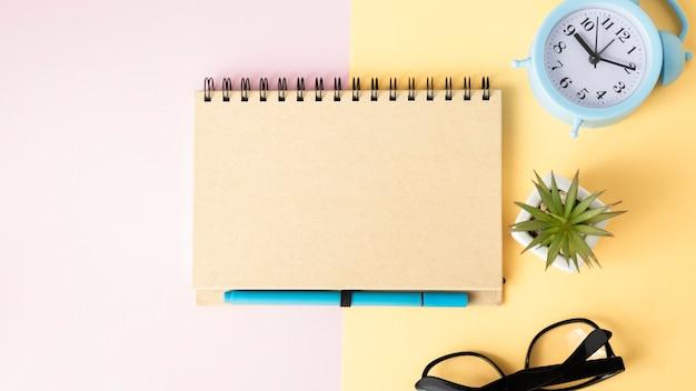 Bovenaanzicht van kladblok, wekker, pen, bril en groene plant op geel en roze