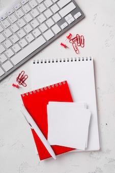 Bovenaanzicht van kladblokken op bureau met pen en toetsenbord