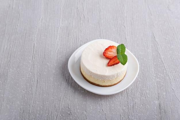 Bovenaanzicht van klassieke cheesecake gegarneerd met aardbeien en munt.