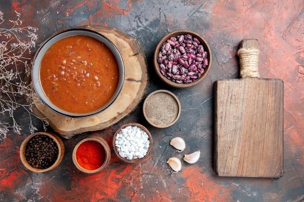 Bovenaanzicht van klassieke tomatensoep op houten dienblad bonen verschillende kruiden en bruine snijplank op gemengde kleurentafel