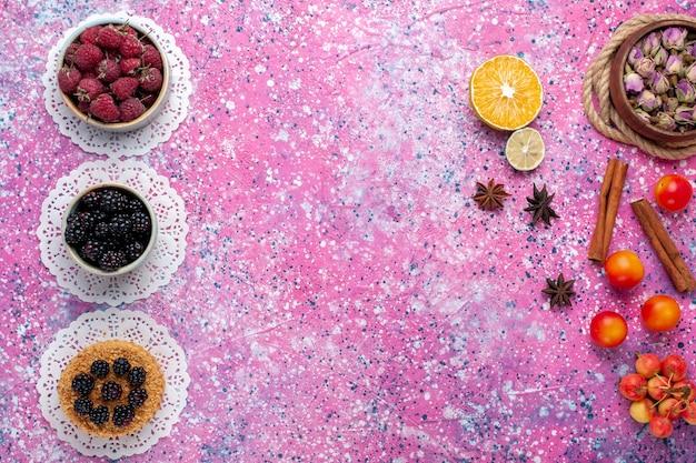 Bovenaanzicht van kleine bramencake met frambozen en verse bramen op het lichtroze oppervlak