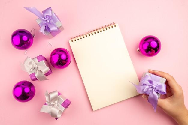 Bovenaanzicht van kleine cadeautjes met kerstboomspeelgoed en kladblok op het roze oppervlak