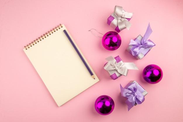 Bovenaanzicht van kleine cadeautjes met kladblok en speelgoed op roze ondergrond