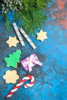 Bovenaanzicht van kleine cadeautjes met snoepjes op blauwe ondergrond