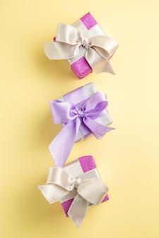 Bovenaanzicht van kleine cadeautjes op lichtgeel oppervlak