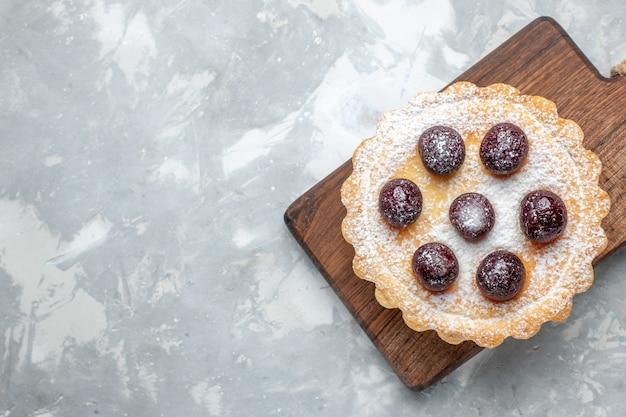 Bovenaanzicht van kleine cake met kersen en suikerpoeder op wit bureau, cake koekje fruit zoete suiker