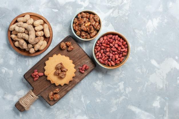 Bovenaanzicht van kleine cake met pistachenoten en noten op lichte witte ondergrond