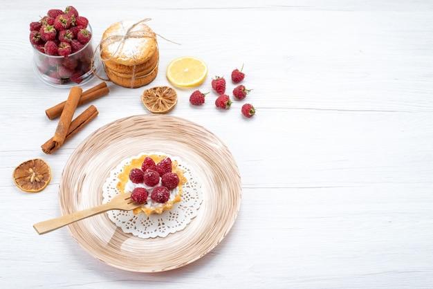 Bovenaanzicht van kleine cake met room en frambozen samen met sandwich koekjes kaneel op licht bureau, fruit bessen cake koekje zoet