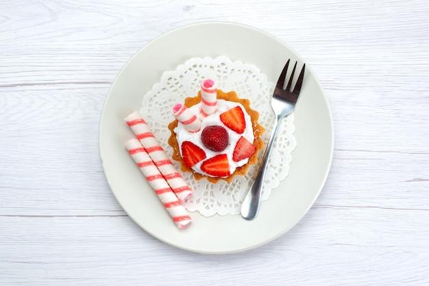 Bovenaanzicht van kleine cake met room en gesneden aardbeien in plaat op wit, fruit cake bessen zoete suiker