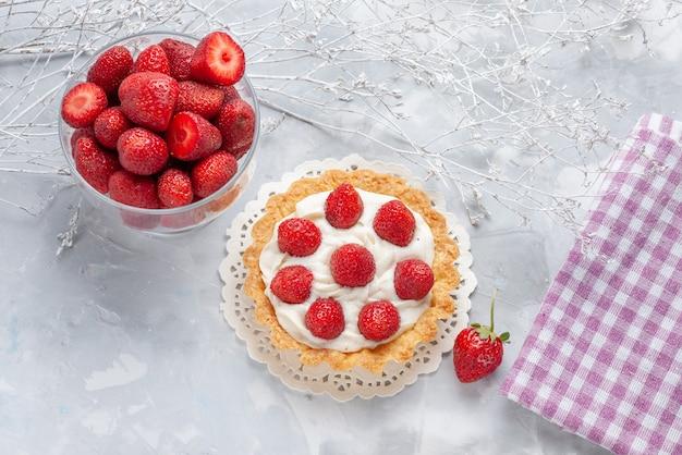 Bovenaanzicht van kleine cake met room en verse rode aardbeien op licht, cake fruit berry biscuit cream