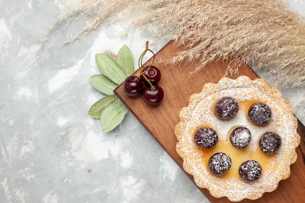 Bovenaanzicht van kleine cake met suiker poeder fruit op licht, cake crème fruit zoet