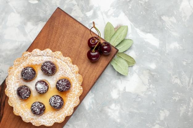 Bovenaanzicht van kleine cake met suiker poeder fruit op licht