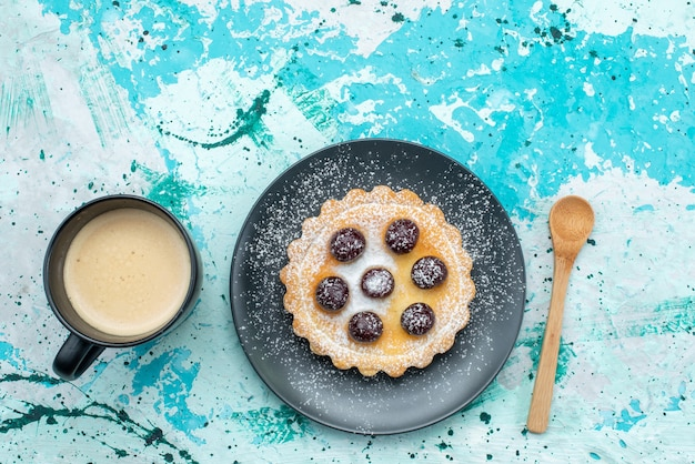 Bovenaanzicht van kleine cake met suikerpoeder en fruit samen met melk op blauw-licht bureau, cake pie fruit zoete suiker