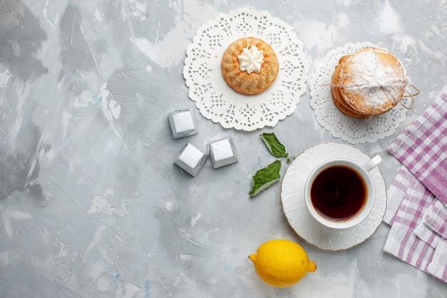 Bovenaanzicht van kleine cake met theesandwichkoekjes en zure citroen op lichte bureau, zoete het koekje van het cakekoekje