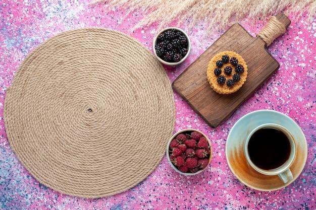 Bovenaanzicht van kleine cake met verschillende bessen en kopje thee op roze oppervlak