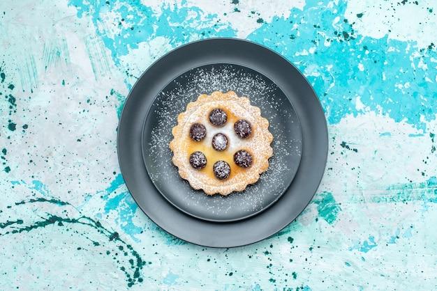 Bovenaanzicht van kleine cake suiker gepoederd met fruit in plaat op blauw licht bureau, cake fruit bakken zoet