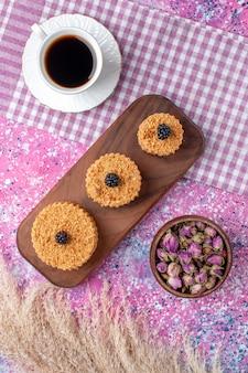 Bovenaanzicht van kleine cakes met kopje thee op roze oppervlak