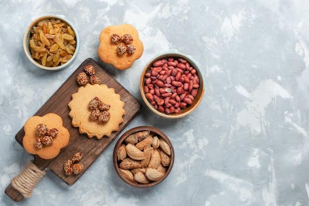 Bovenaanzicht van kleine cakes met pistachenoten en noten op lichte witte ondergrond Gratis Foto