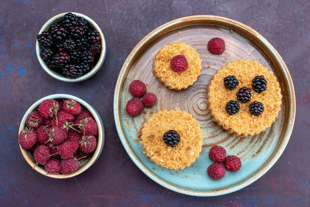 Bovenaanzicht van kleine cakes, zoet en lekker met verse bessen op donkere ondergrond