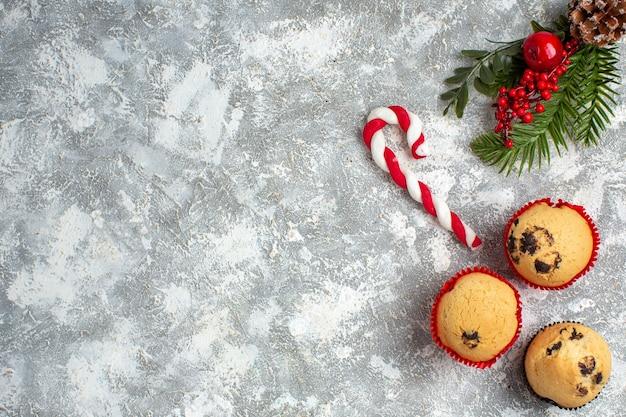 Bovenaanzicht van kleine cupcakes, snoep en dennentakken, decoratieaccessoires, coniferenkegel aan de rechterkant op ijsoppervlak